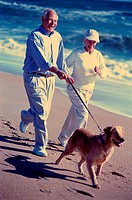 Senior couple jogging with their dog on the beach