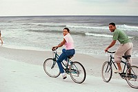 Young couple cycling on the beach