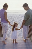 Portrait of a girl holding her parents hands on the beach