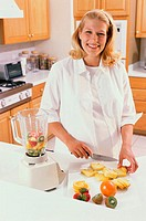 Portrait of a pregnant woman cutting fruit