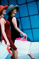 Side profile of two young women walking with shopping bags