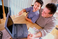 High angle view of a father and his son sitting in front of a laptop holding a credit card