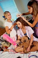 Two teenage girls styling their friend´s hair