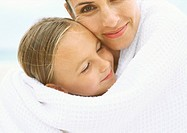 Mother and daughter wrapped in towel, portrait