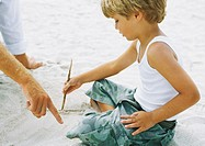 Boy sitting on sand, drawing with stick, father pointing