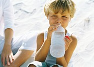 Boy sitting on sand next to mother, drinking water