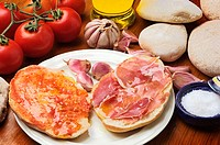 Mediterranean food: 'molletes de Antequera' (typical bread) with cured ham, oil, tomatoe, salt and garlic. Andalusia, Spain
