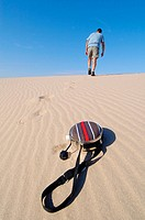 Slouching man walk up sand dune after throw away canteen. Mojave Desert. California. USA