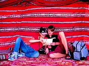 Western tourist couple sitting in Arabian tent reading a map, United Arab Emirates