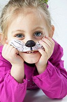 Young girl with bodypaint, cat nose painted in face.