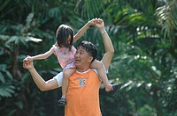 Girl sitting on her father´s shoulders, Malaysia