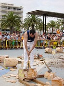 ´Aizkolari´ man cutting log with an axe, demonstration of ´aizkora´ (traditional Basque sport). Salou, Tarragona province. Catalonia, Spain
