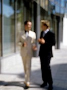 blurred image of two businessmen having a conversation