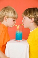 Two little boys drinking blue lemonade through straws out of the same glass sharing