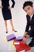 Man picking up folders for woman
