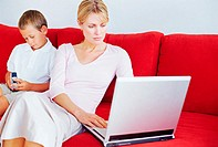 Mother and son using laptop and mobile phone