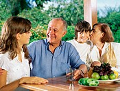 Children and grandparents at table outdoors