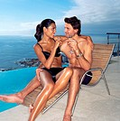 Couple on a sunlounger with champagne