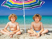 Twin boys under a sun umbrella