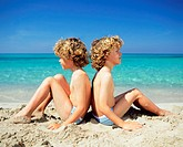 Twin boys sitting on the beach