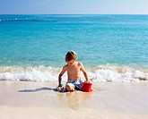 Boy playing with wet sand
