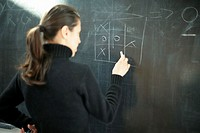 Young woman drawing noughts and crosses on a blackboard