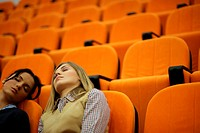 Two young women asleep in a lecture theatre
