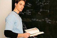 Young man standing in front of a blackboard