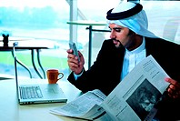 Arab businessman checking his mobile phone in the office
