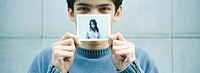 Young man holding up photo of young woman
