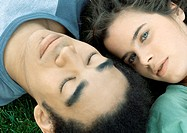 Young couple lying on grass together, close-up