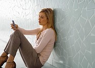 Woman sitting on floor, leaning against wall and looking at cell phone