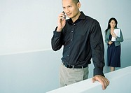 Man using cell phone, woman standing behind him