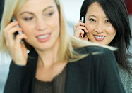 Businesswomen using cell phones, portrait