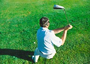 Golfer swinging, high angle view