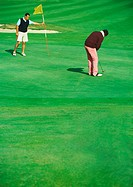 Golfer putting while second man holds golf flag
