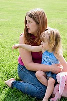Young daughter sitting on her mother's lap at the park