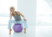 A woman sitting on an exercise ball, smiling