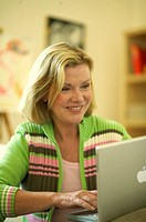A woman typing on a laptop keyboard, smiling