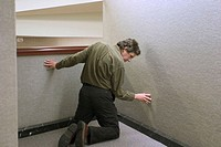 Man kneeling against a wall in an office building.