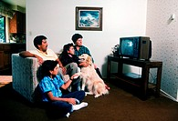 Hispanic family and pet dog at home watching T.V.