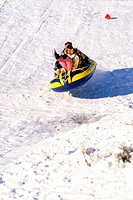People sledding in the snow on an inflatable raft.