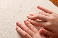 Blind high school student´s hands reading Braille.