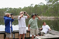 Male, birders, binoculars, coastal estuary. Audubon Bird Sanctuary, Dauphin Island. Alabama. USA.