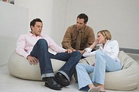 three people sitting on bean bags having a conversation