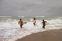 Surfing hurricane Katrina. Three young surfers head to sea to surf waves caused by the approaching hurricane Katrina. Photographed on 25th August 2005...