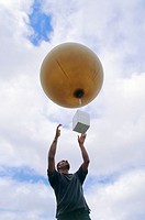 Weather balloon being released by a meteorologist. It contains helium gas, allowing the balloon to rise many kilometres through the atmosphere. A sens...