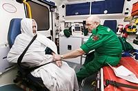 Ambulance treatment. Ambulance technician taking an elderly male patient´s pulse.