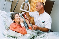 EDITORIAL USE ONLY. Terminal care. Hospital nurse helping a terminally ill patient to apply make-up. Terminal, or palliative, care is the active total...