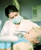 Dental anaesthetic. Dental worker injecting a local anaesthetic into the gum of a patient´s tooth. This will numb the gum to allow a simple surgical p...